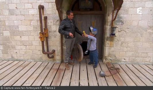 Fort Boyard 2014 : Passe-Muraille remet le premier parchemin à Olivier Minne lors d'une scénette où il peut se déguiser